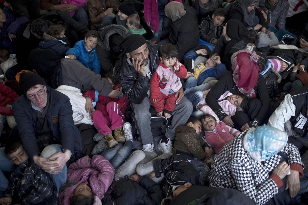 A man sits inside a tent surrounded by sleeping children at the refugee camp in Idomeni, Greece, March 7, 2016.