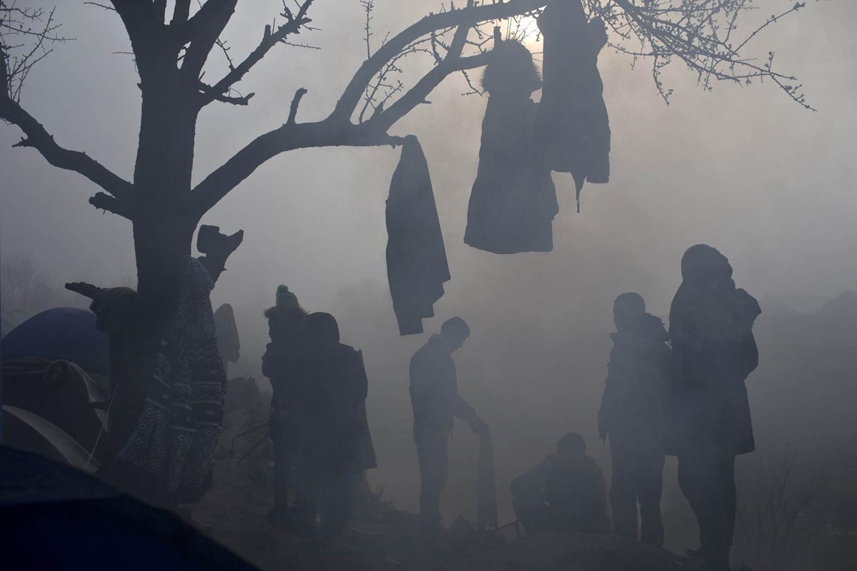 A Kurdish family try to stay warm by burning excess clothes as fog engulfs the refugee camp in Idomeni, Greece, March 8, 2016.