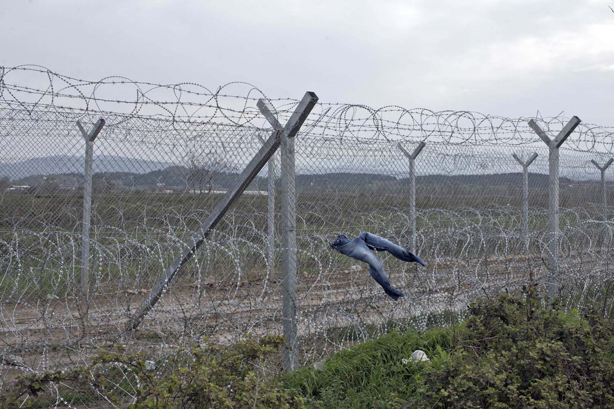 A pair of jeans are dried on the border fence between Greece and Macedonia, at the refugee camp in Idomeni, Greece, March 25, 2016.