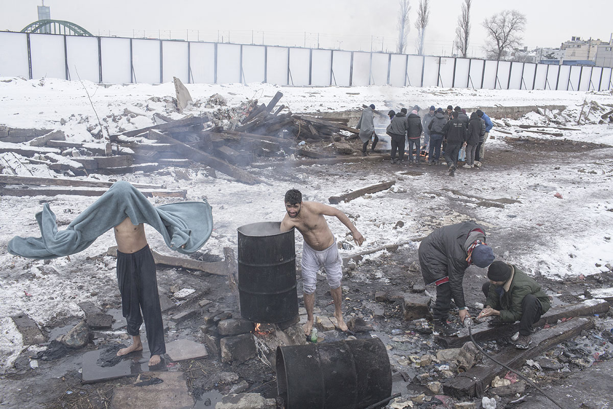 People take a bath while heating water in an old oil drum, Belgrade, Serbia, Jan. 19, 2017.