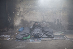 A man wakes up  inside a decrepit warehouse he and others use as shelter, Belgrade, Serbia, Jan. 19, 2017.