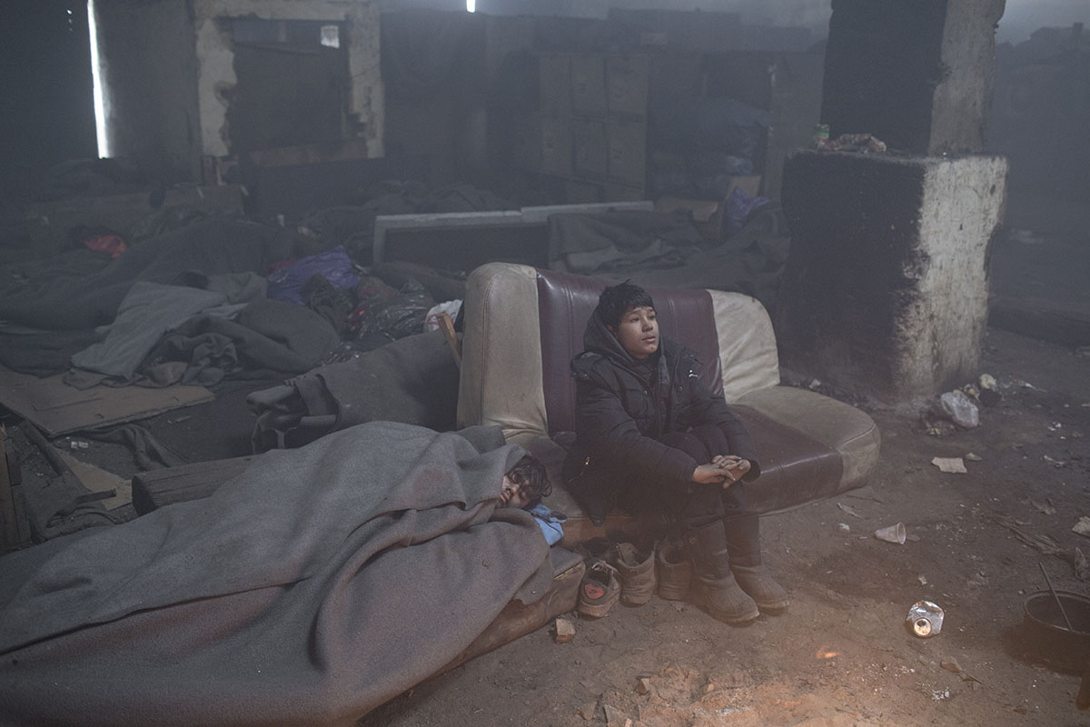 Qutratullah, 12, a young boy from Afghanistan, warms himself by the fire inside a warehouse, Belgrade, Serbia, Jan 26, 2017.
