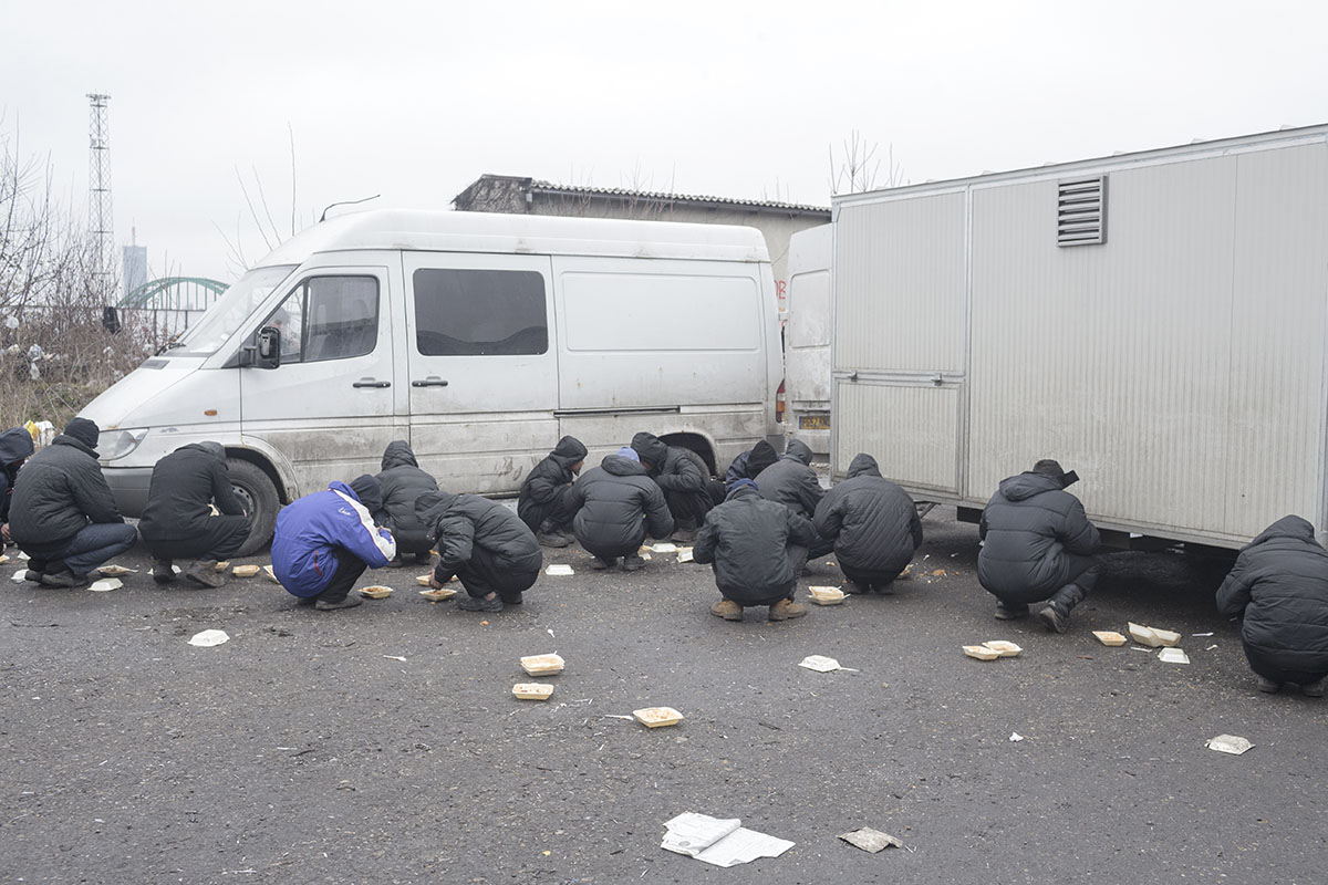 Refugees squat as they eat a meal provided by volunteers, Belgrade, Serbia, Feb. 7, 2017.