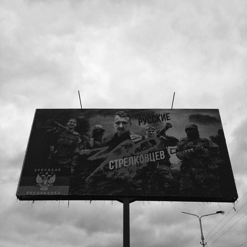 june 12, 2014. a billboard, artemivsk, ukraine. on the road to slovyansk. i eat kit kats. m. eats snickers. a smokes his pipe.