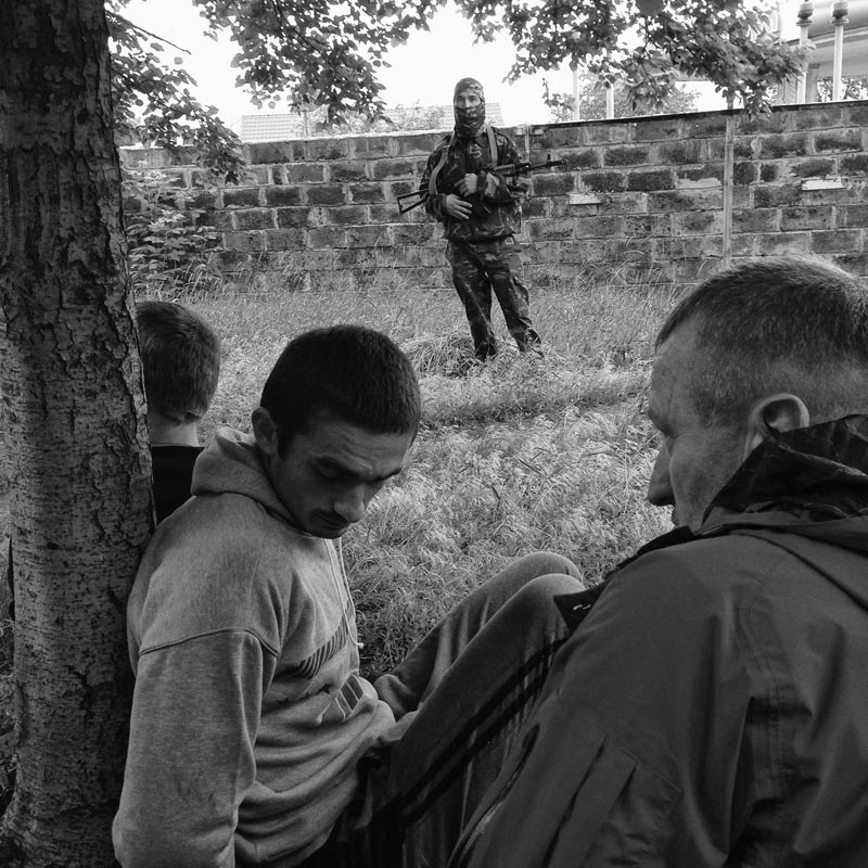 June 12, 2014. Suspected marauders, Slovyansk, Ukraine. Another three-hour drive through villages. This time three checkpoints. Ukrainian army in APC's stationed in a forest by the side of the main road. A. turns the minivan back. We decide we have to go in. I tell everybody to put flak jackets on. People downtown so traumatized I tell everybody to take flak jackets off. A. wants to visit his aunt and deliver water for her family. As we wait for him to descend from the apartment, shelling starts. Flack jackets back on.