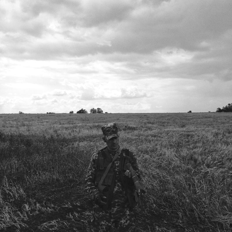 June 14, 2014. A member of a pro-Russian militia stands in a field of wheat, Lugansk, Ukraine. Noone knows where the plane is. Flak jackets on. Something feels strange. I tell A. to drive slowly. We get ambushed by pro-Russians who turn out to be friendly. They take us to the plane.