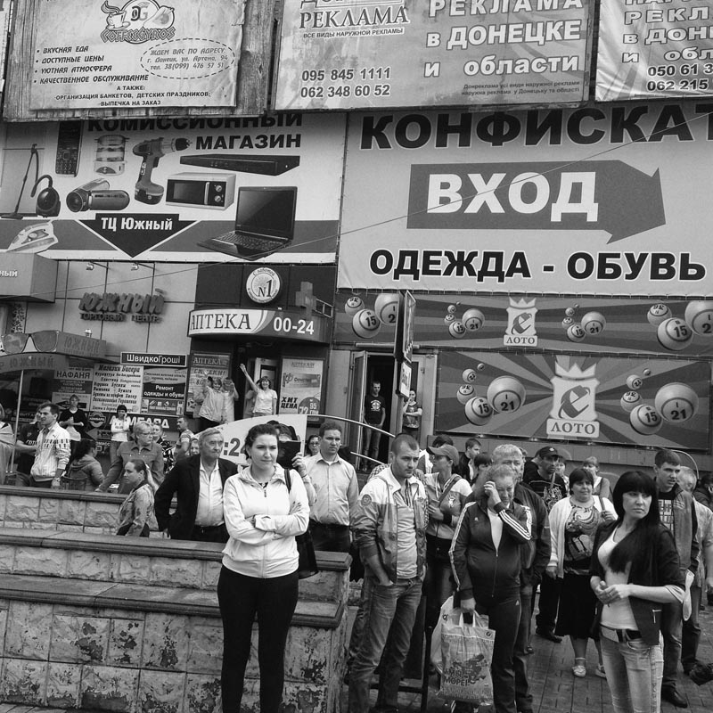 June 18, 2014. People on a street, Donetsk, Ukraine. I follow a miner with a lot of medals carrying a red flag on his shoulder. He knows Yugoslavia, been there in the 60's.