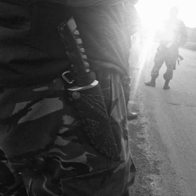 june 18, 2014. pro russian militiamen, karlovka, ukraine. we see v. downtown, he tells us something is happening in karlovka. on the way there we stop so a. can buy fish from an old lady by the side of a road in a forest. alfa romeo, lithuanian license plates, gets my attention. a big tall dude in camo gets out, invites us to see an exchange of dead bodies by two sides on the line of separation. bmw, russian license plates parks next to a.'s minivan. a guy in a balaclava gets out, takes a rpg out of the trunk, leans it on the side of the car. flak jackets on.