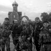 june 18, 2014. pro russian militiamen, karlovka, ukraine. sun sets. two sides at war meet on a road bridge over a body of water. ukrainians wave a white flag. bodies are exchanged. huge white cross at background. we finish filming. the guys ask us to take their photo after it's done. very friendly bunch. on our way back, a drunk man fires a warning shot in the direction of a.'s minvan. a. tells him to fuck off, then lights his pipe.