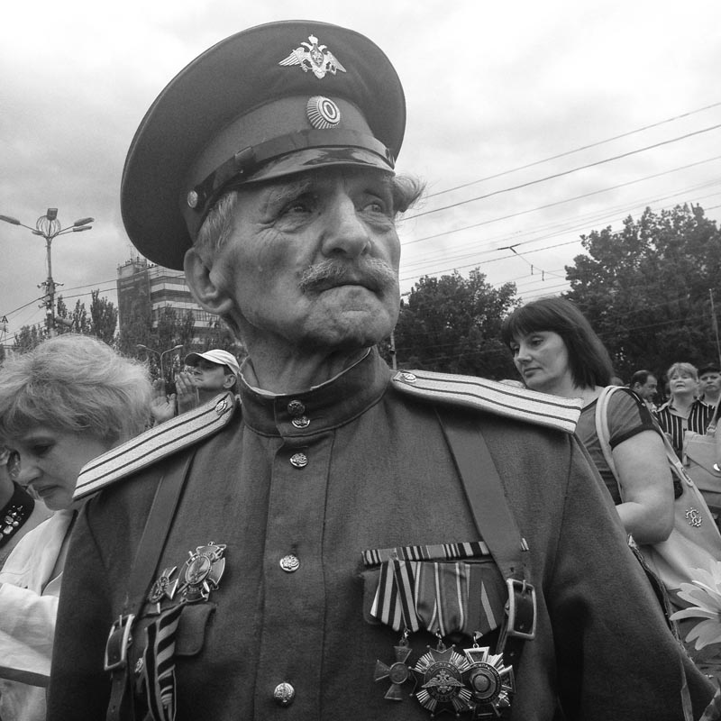 june 21, 2014. a war veteran, donetsk, ukraine. i start talking serbian, the guy lets us be. an amazing old veteran with medals appears briefly from the crowd. i take two photos, he disappears. can't find him.