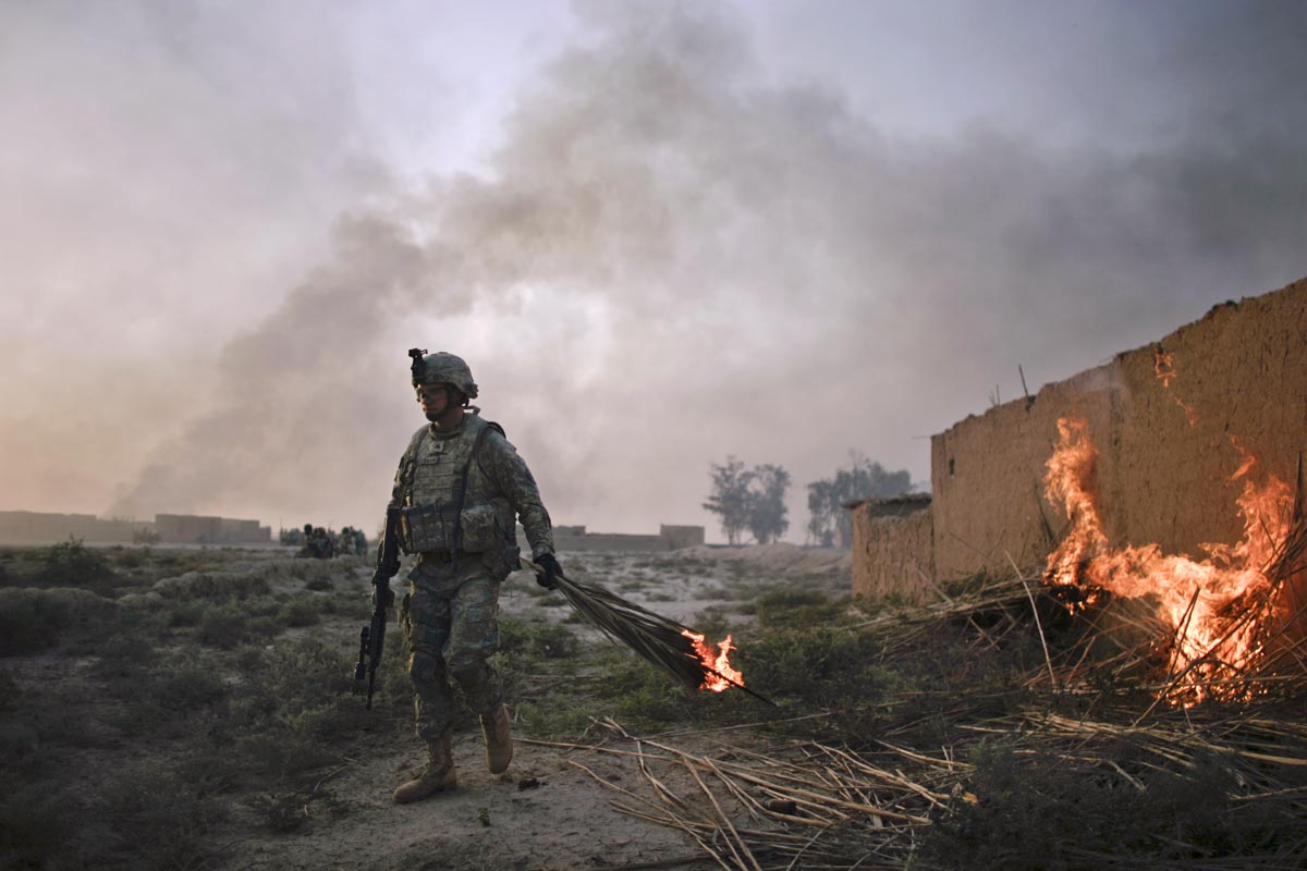 a u.s. army soldier from fox troop, sabre squadron, 3rd armored cavalry regiment, sets an abandoned house on fire, diyala province, iraq, 2008.