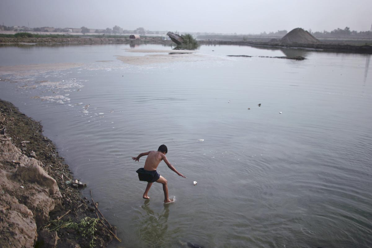 a child jumps into the tigris, baghdad, iraq, 2008.