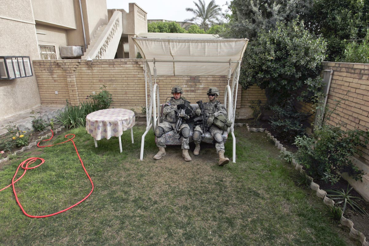 U.S. army soldiers from Blackhawk Company, 1st Battalion, 23rd Infantry Regiment, take a break inside a garden of a house, Baghdad, Iraq, 2007.