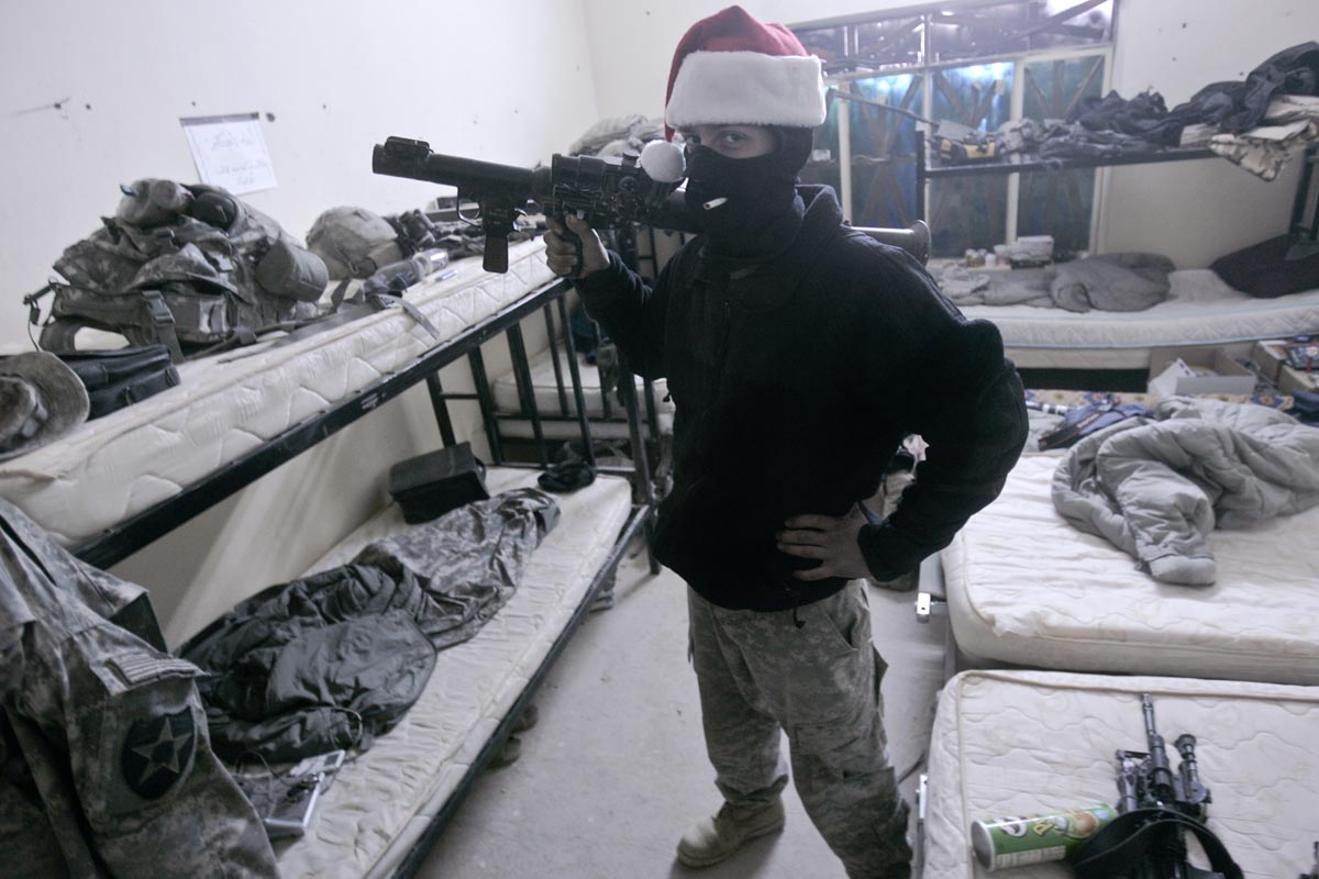 A U.S. army soldier from Blackfoot Company, 2nd Battalion, 23rd Infantry Regiment poses for a photograph while wearing a balaclava and a Santa hat and carrying a confiscated RPG launcher, Diyala province, Iraq, Christmas, 2007.