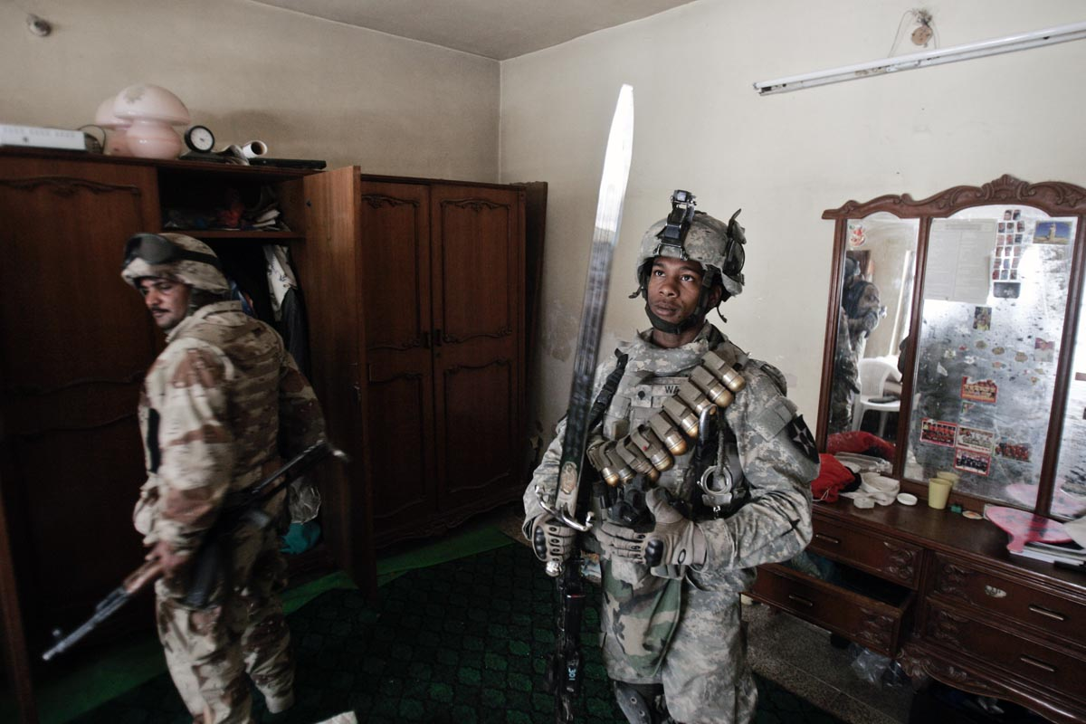 a u.s. army soldier from blackhawk company, 1st battalion, 23rd infantry regiment, admires a sword he found while searching a home, baghdad, iraq, 2007.