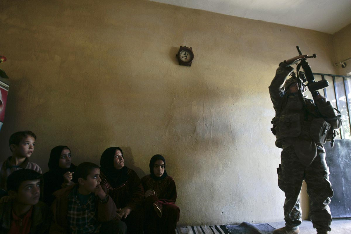 a u.s. army soldier from blackfoot company, 2nd battalion, 23rd infantry regiment, adjusts his weapon during a house search, diyala province, iraq, 2007.