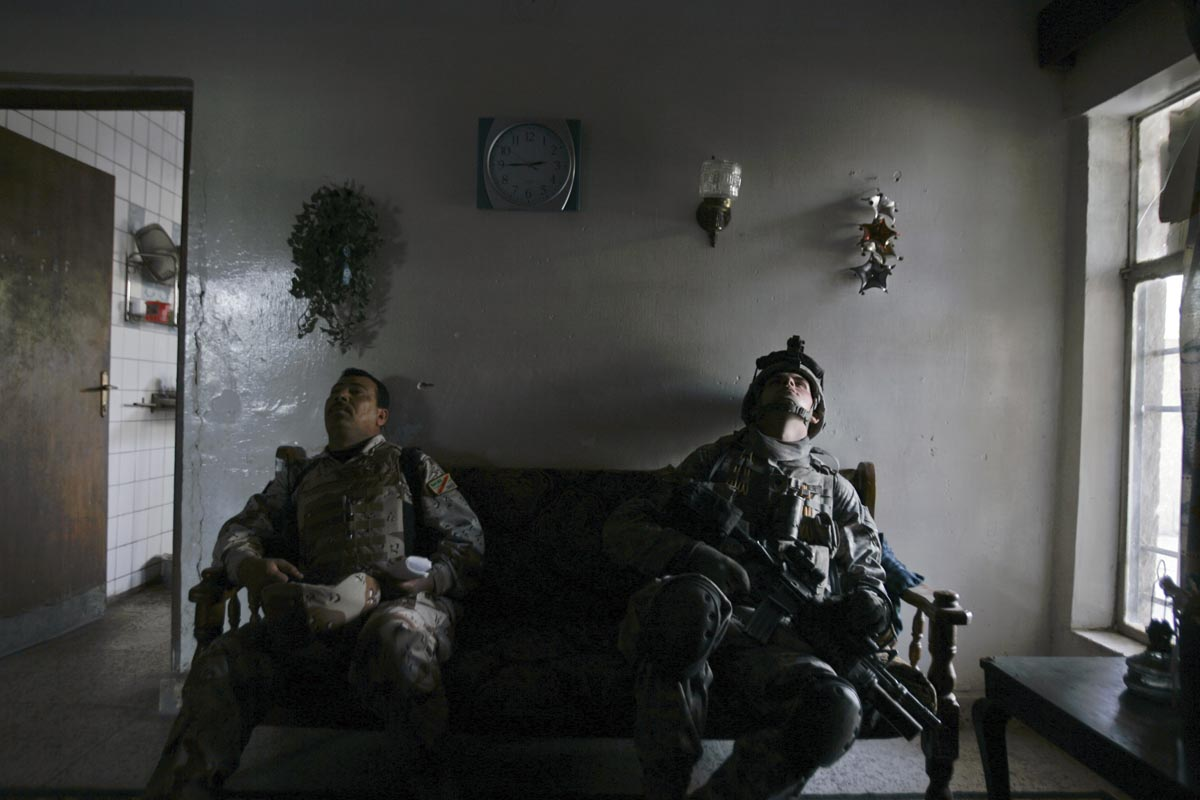 a u.s. army soldier from blackhawk company, 1st battalion, 23rd infantry regiment and his iraqi colleague take a break during a house search, baghdad, iraq, 2007.