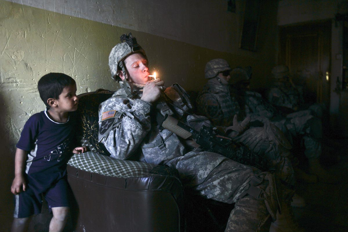 a u.s. army soldier from blackhawk company, 1st battalion, 23rd infantry regiment, lights a cigarette, baghdad, iraq, 2007.