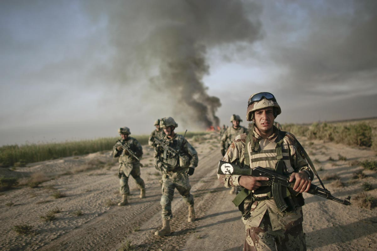An Iraqi army soldier conducts a foot patrol together with U.S. army soldiers from Fox Troop, Sabre Squadron, 3rd Armored Cavalry Regiment, after they set a deserted village on fire, Diyala province, Iraq, 2008.