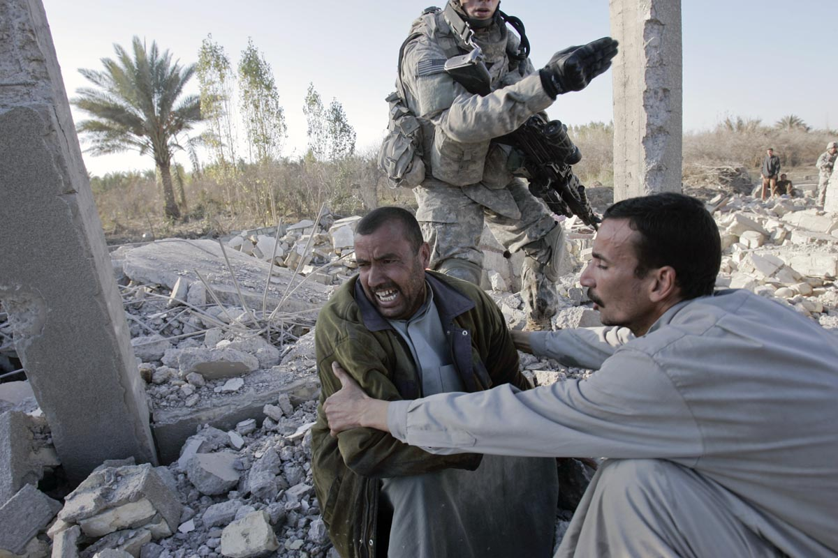 a man cries as he sits on the rubble of his house, destroyed by a u.s. missile, diyala province, iraq, 2007.