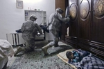 a boy sleeps in his home as u.s. army soldiers from blackhawk company, 1st battalion, 23rd infantry regiment, search his room, baghdad, iraq, 2007.