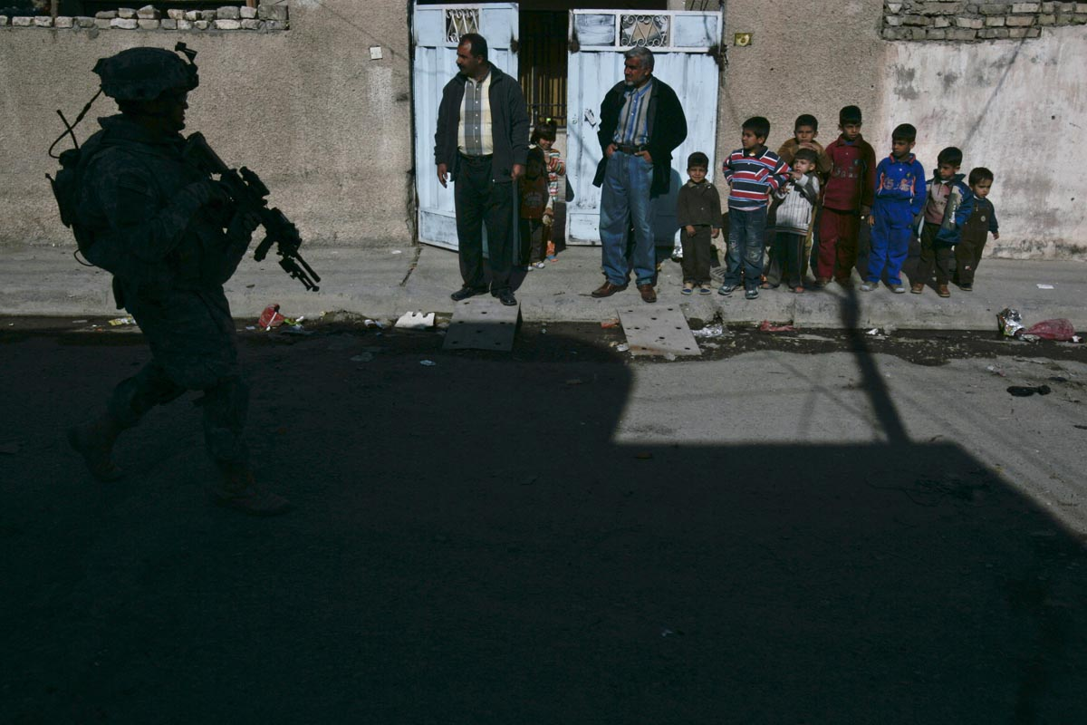 a family stands outside their home as u.s. army soldiers from able company, 4th battalion, 9th infantry regiment, patrol their street, baqouba, iraq, 2007.