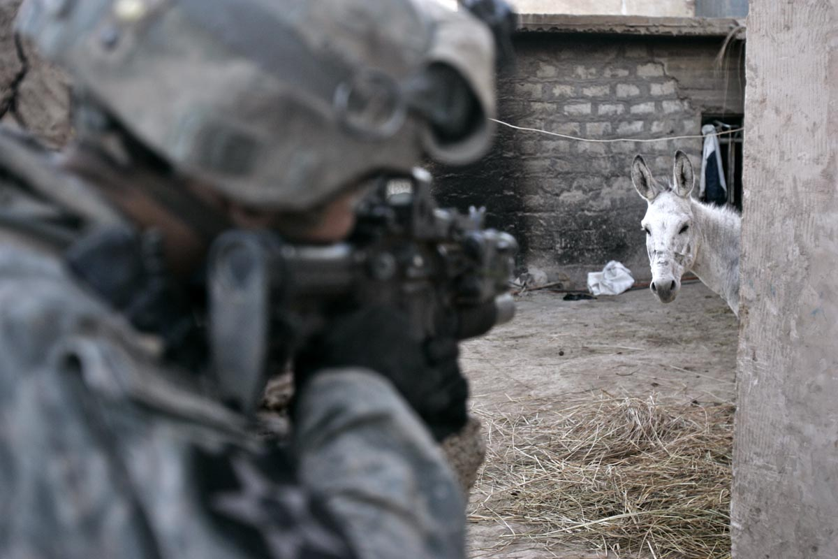 a u.s. army soldier from blackfoot company, 2nd battalion, 23rd infantry regiment storms a back yard of a house during an offensive, muqdadiyah, iraq, 2007.