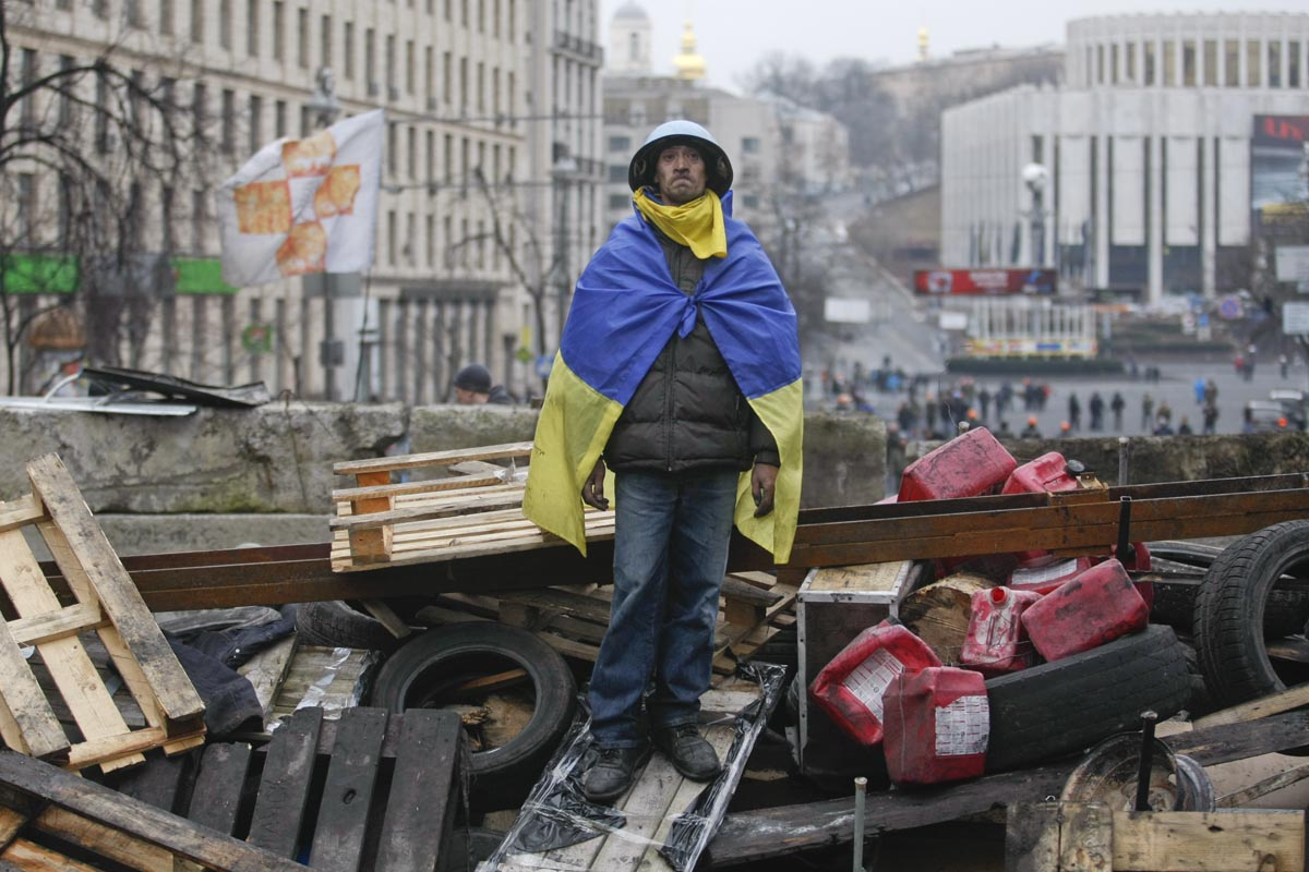 a man stands atop a barricade, kiev, ukraine, feb. 20, 2014.