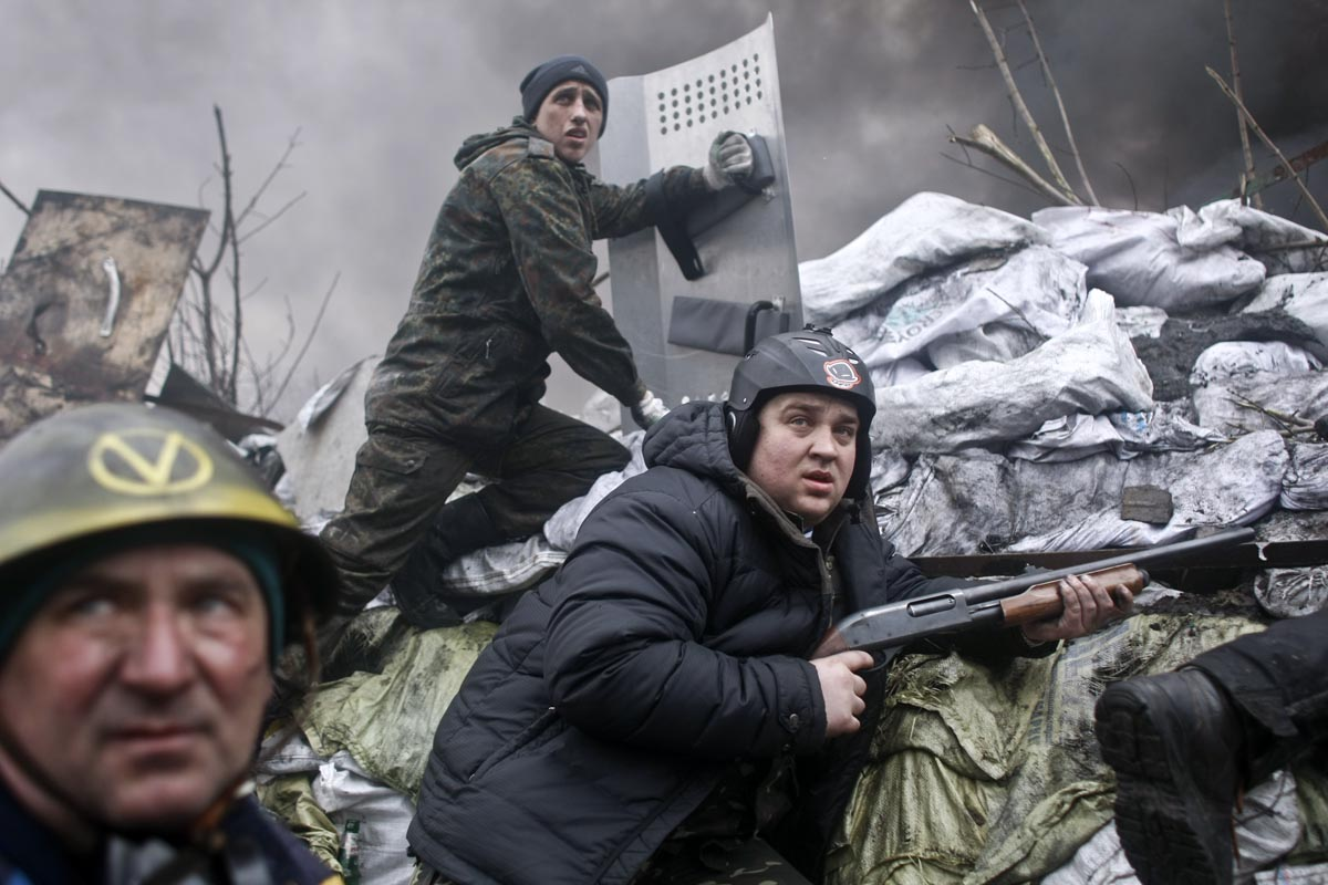 armed supporters of the opposition prepare to fire at police positions, kiev, ukraine, feb. 20, 2014.