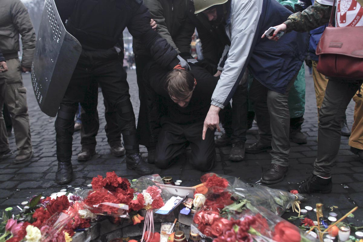 a suspected regime collaborator is made to kneel and pay respect to victims of clashes, kiev, ukraine, feb. 22, 2104.