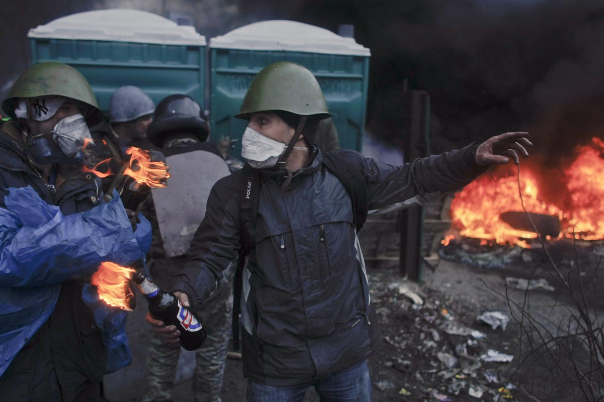 a youth gets ready to throw a molotov cocktail at government positions, kiev, ukraine, feb. 20, 2014.