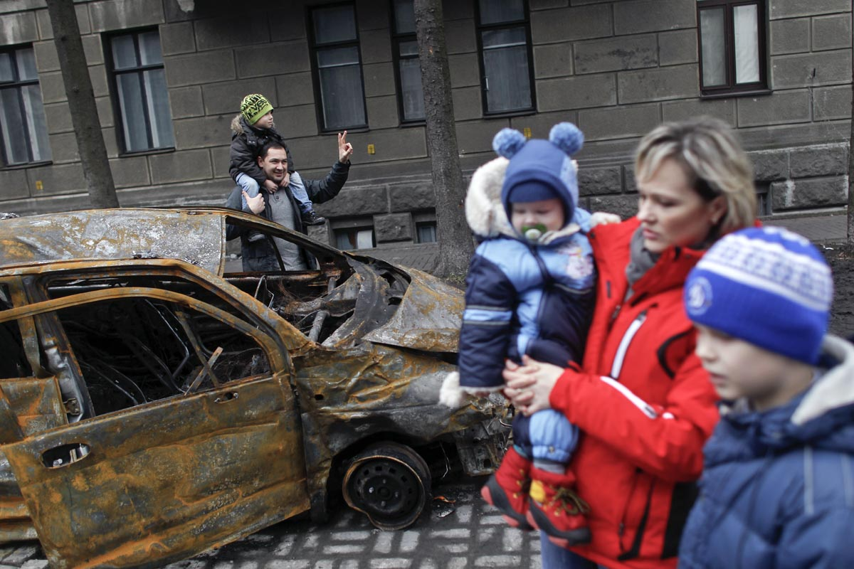 People pose for photographs next to a car burned during protests, Kiev, Ukraine, Feb. 22, 2014.