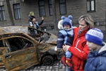 people pose for photographs next to a car burned during violent protests, kiev, ukraine, feb. 22, 2014.