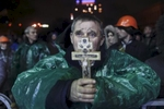 a man holds a cross as he prays, kiev, ukraine, feb. 20, 2014.