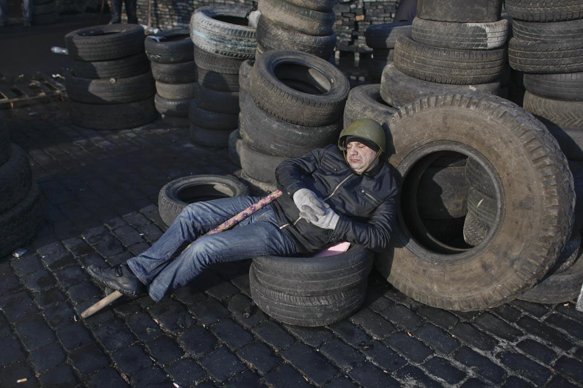 A protester sleeps at a barricade, Kiev, Ukraine, Feb. 21, 2014.