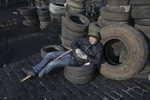 a protester sleeps at a barricade, kiev, ukraine, feb. 21, 2014.