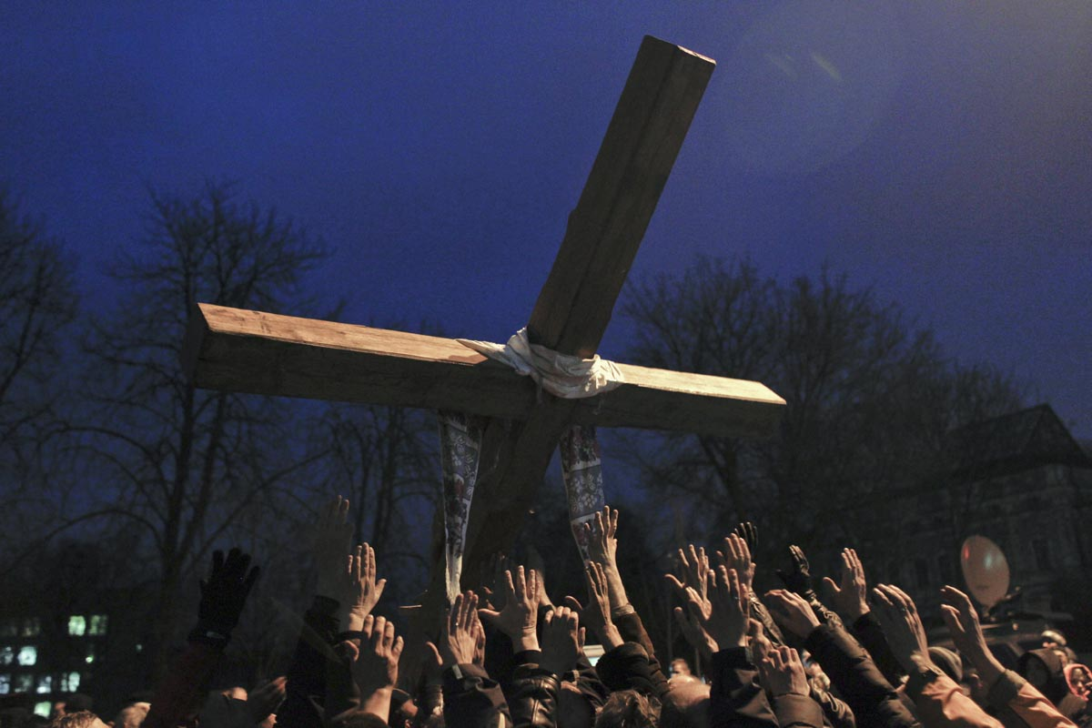 People lift a cross during a religious procession, Kiev, Ukraine, Feb. 24, 2014.