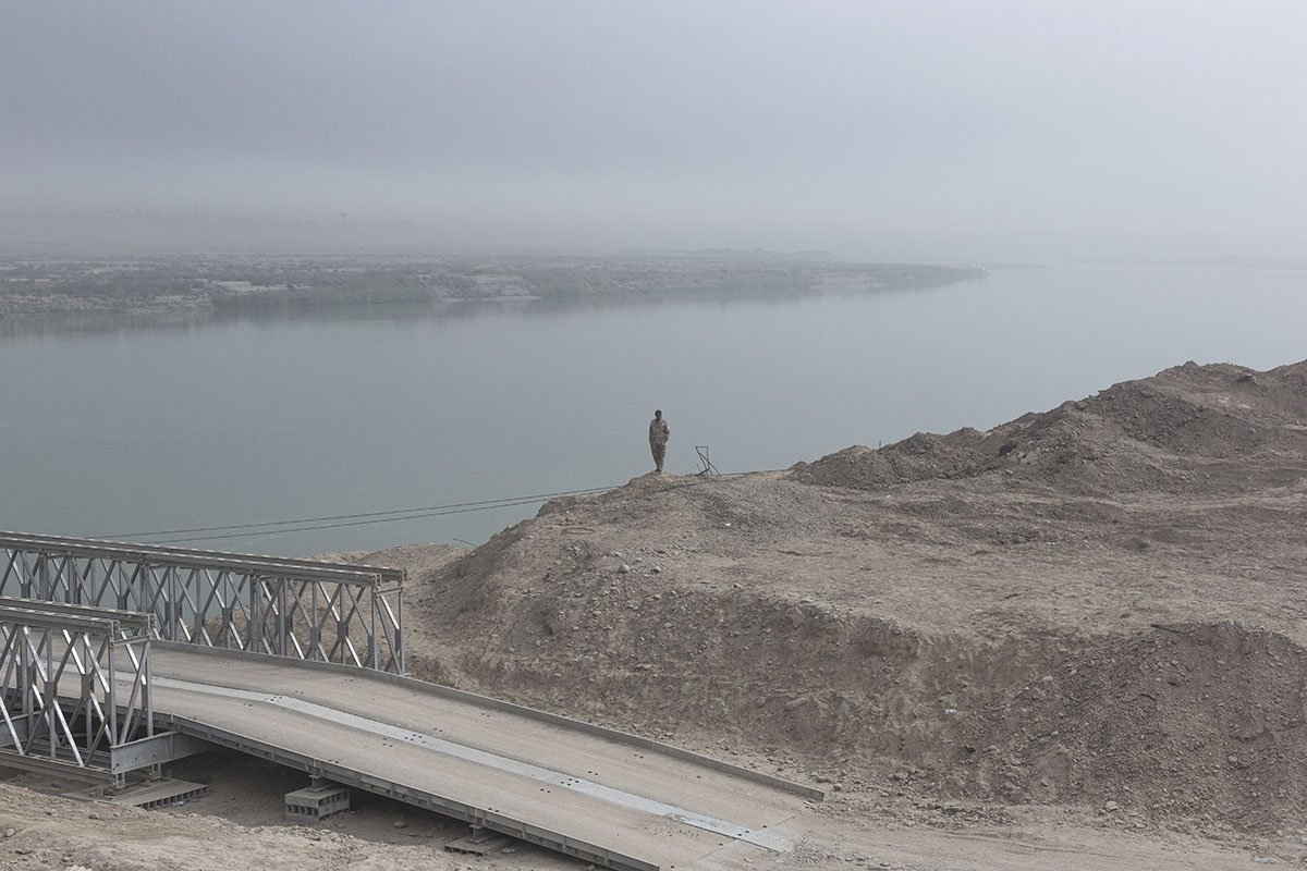 An Iraqi army soldier stands at the banks of the Tigris, Qayara, south of Mosul, Iraq, Nov.10, 2016.