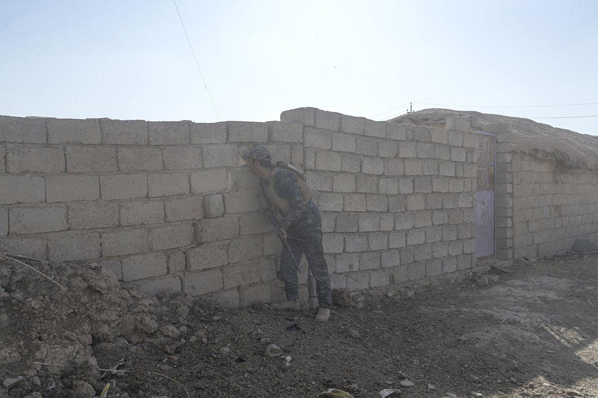 An Iraqi federal policeman scans an enclosure through a crack in a wall, Shura, south of Mosul, Iraq, Oct. 29, 2016.