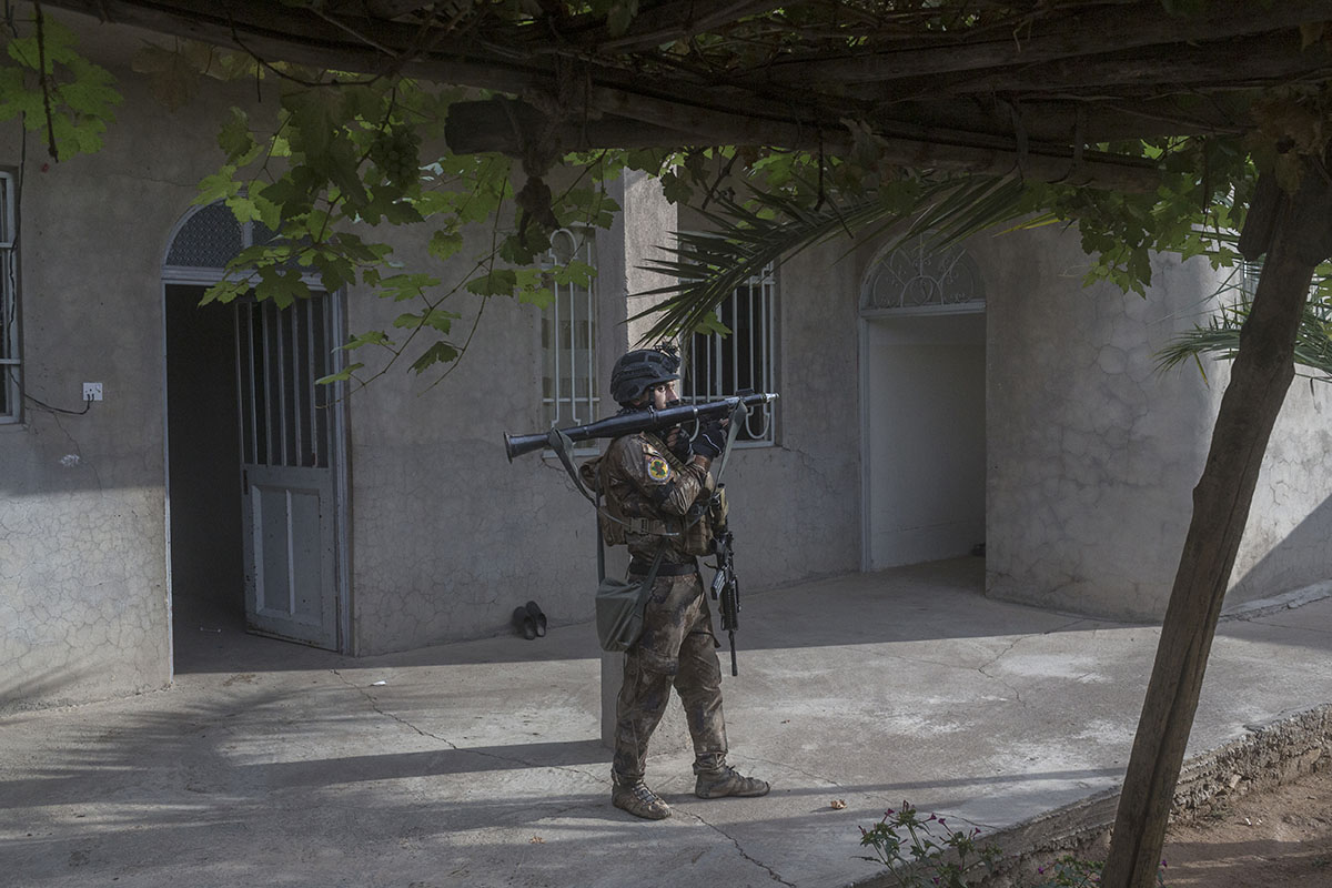 An Iraqi special forces soldier stands inside a courtyard while his unit searches a home, Gogjali, outskirts of Mosul, Iraq, Nov. 2, 2016.