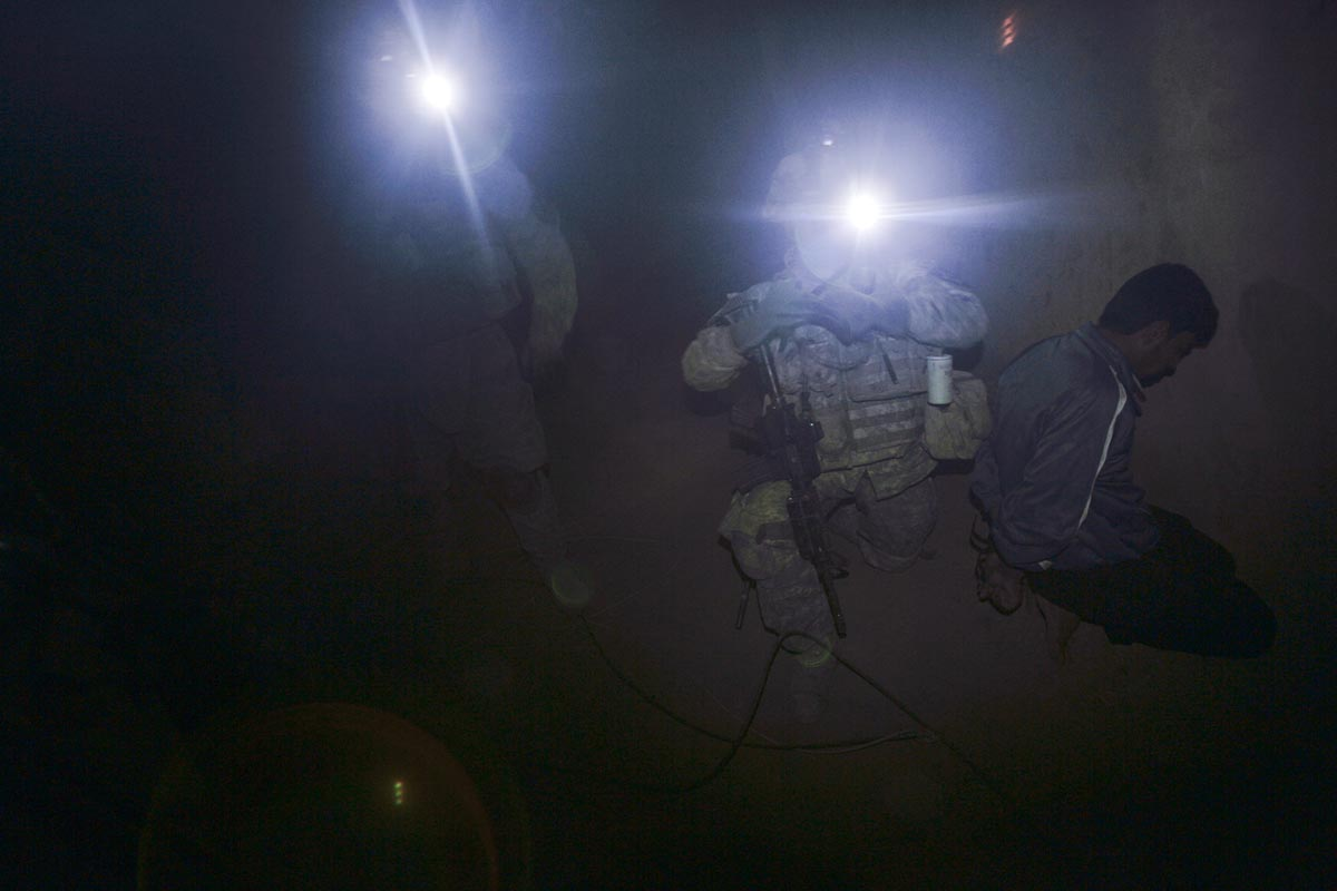U.S. army soldiers from Blackfoot Company, 2nd Battalion, 23rd Infantry Regiment, detain a man during a night raid, Diyala province, Iraq, 2007.