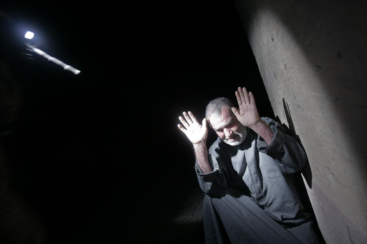 a man raises his hands as he is held at gunpoint by u.s. army soldiers from blackfoot company, 2nd battalion, 23rd infantry regiment, while they conduct a night raid on the outskirts of muqdadiyah, diyala province, iraq, 2007.
