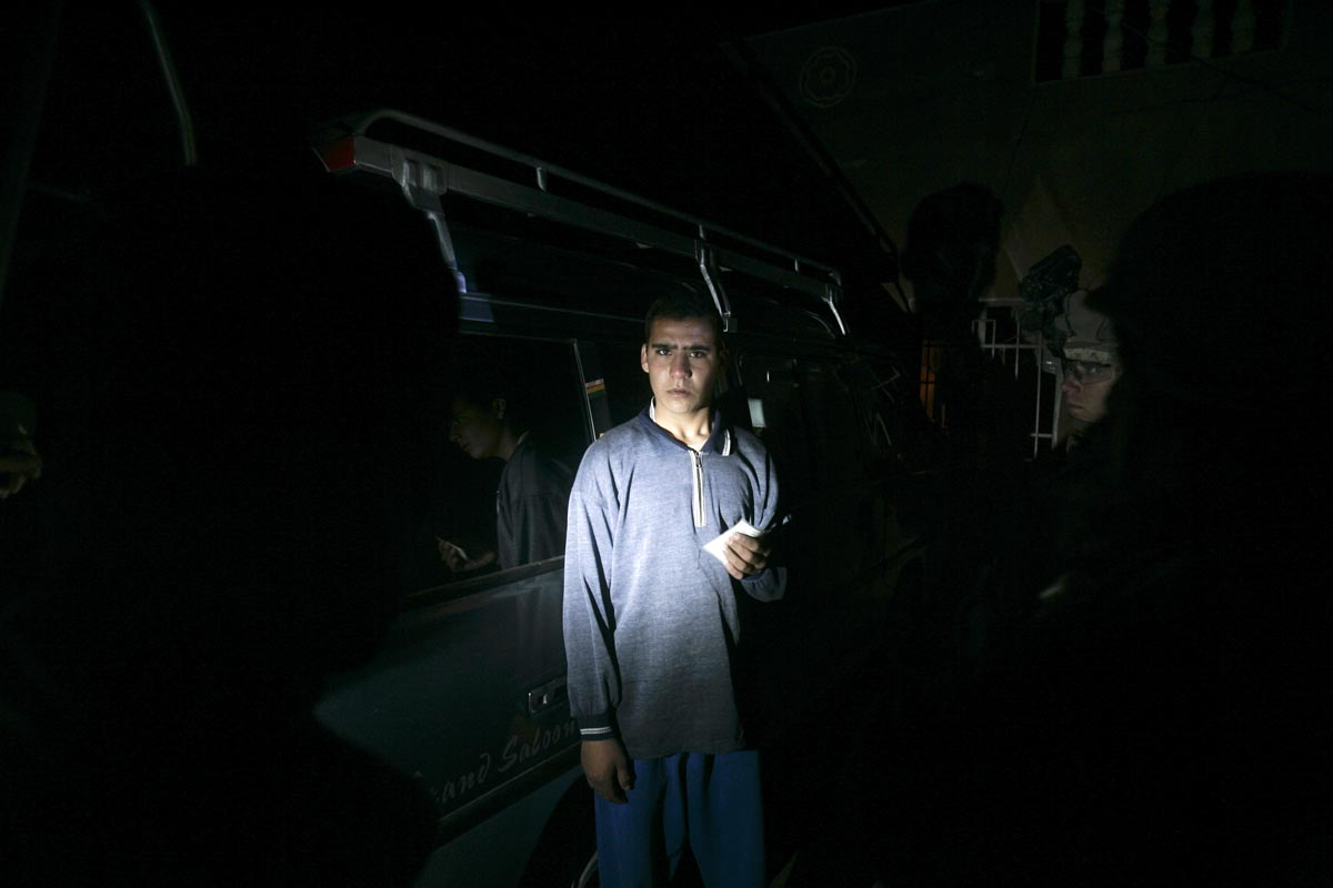a youth holds his identity card as he is interrogated by u.s. army soldiers from blackfoot company, 2nd battalion, 23rd infantry regiment, diyala province, iraq, 2007.