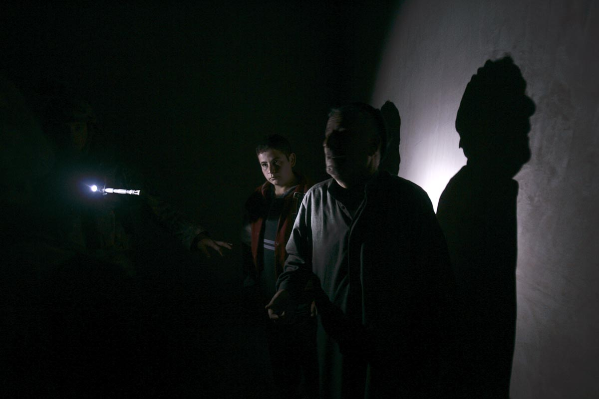 u.s. army soldiers from blackfoot company, 2nd battalion, 23rd infantry regiment, interrogate a man during a night raid, diyala province, iraq, 2007.