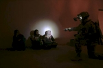 a u.s. army soldier from blackfoot company, 2nd battalion, 23rd infantry regiment, interrogates a family in their home during a night raid, diyala province, iraq, 2007.