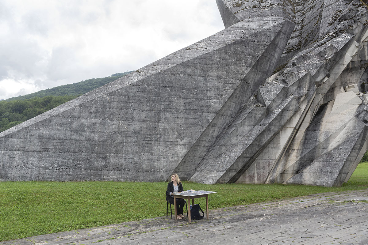 A souvenir seller waits for customers as she sits next to a monument to the WWII Battle of the Sutjeska, Tjentiste, Bosnia and Herzegovina, June 17, 2017. Thousands of monuments of all shapes and sizes were erected in Yugoslavia throughout the 1960's and 1970's to commemorate important historical events and WWII battles. A large number of the monuments were heavily damaged or destroyed on purpose in the 1990's conflicts. Those that survived are still visited by Yugoslavs and people who feel nostalgia for the old country.