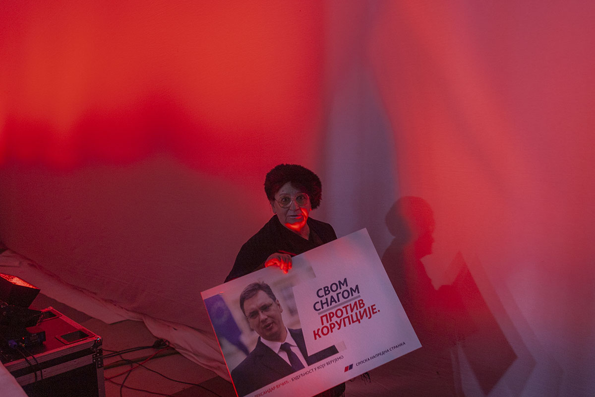 A woman attends an election rally and holds a poster depicting Aleksandar Vucic, a populist candidate with a strong nationalist agenda, who would later become Serbian prime minister and president, Belgrade, Serbia, March 3, 2014. In the 1990's, Vucic was a prominent member of a Serbian ultranationalist political party tied to war crimes committed during the Yugoslav wars.