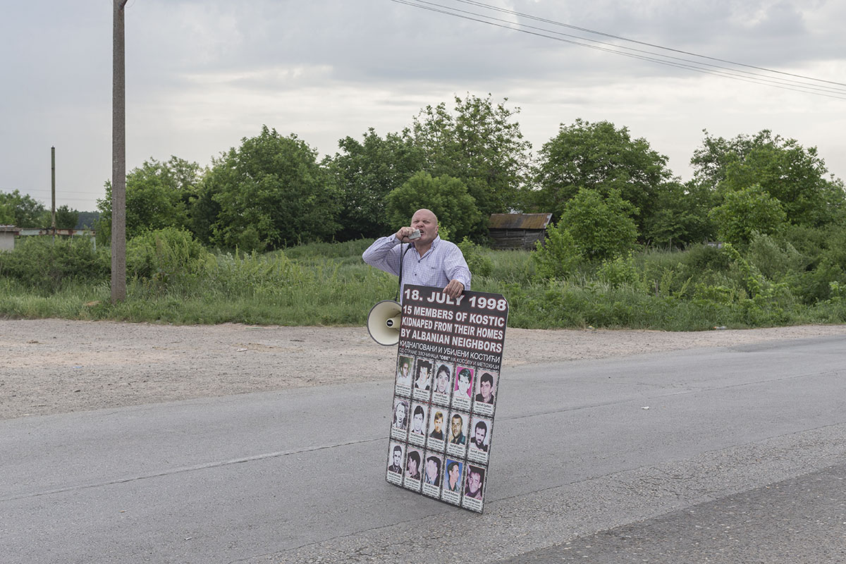Simo Spasic, the president of the Association of families of kidnapped and murdered persons in the 1998-1999 Kosovo war, speaks through a bullhorn during a Serbian ultranationalist gathering, Jarak, Serbia, May 6, 2018. Spasic is holding a poster depicting fifteen missing members of the Kostic family, taken from their homes and presumably murdered by ethnic Albanian guerrillas in 1998.