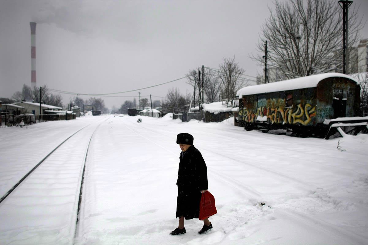 a woman crosses snow covered train tracks, belgrade, serbia, 2011.
