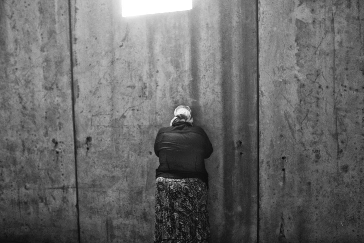 a woman cries as she tries to hide her grief, potocari memorial center, bosnia, 2012.